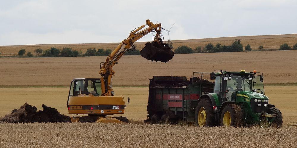 Mistlader mit Traktor auf einem Feld
