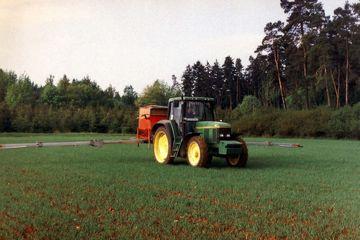 Traktor mit Anbaudüngerstreuer auf Getreidefeld.