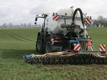 Düngerstreuer beim Ausbringen und Einarbeiten von Gülle auf einem Getreidefeld.