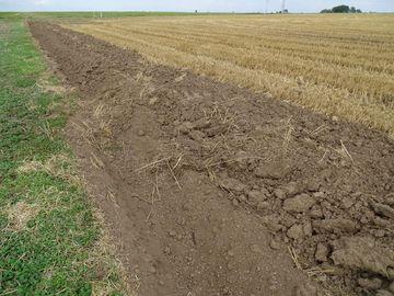 Pflugfurche am Rand eines abgeernteten Getreidefeldes