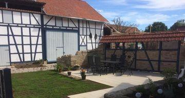 Innenhof eines sanierten Fachwerkhauses mit Terrasse und Garten