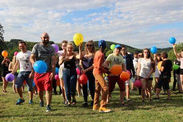 zu sehen ist eine Gruppe von Jugendlichen, die mit Luftballons in den Händen auf die Kamera zulaufen und dabei einen fröhlichen Eindruck machen.