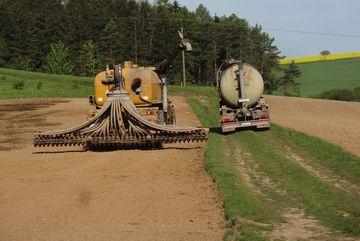 Betanken eines Terra Gator mit Gülle. Terragator steht auf einem abgeernteten Feld. Güllefaß steht daneben auf einem Feldweg.