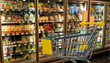 leerer Einkaufswagen vor gefüllten Kühlregalen eines Marktes
