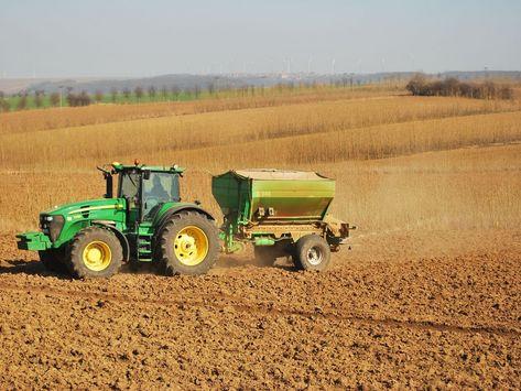 Traktor mit angebautem Düngerstreuer unterwegs auf einem unbewachsenen Feld