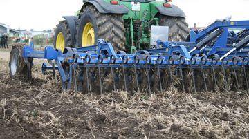 Traktor mit Grubber bei der Feldarbeit