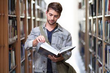 Student mit Buch in der Hand zwischen Bücherregalen