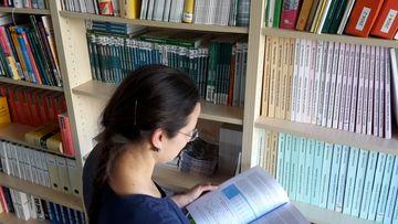 Eine Frau liest ein Buch vor einem Regal